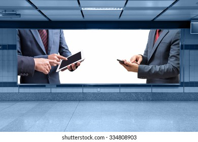 businessmen using tablet and smart phone at meeting display on billboard with white space for advertising