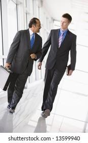 Businessmen walking through office lobby