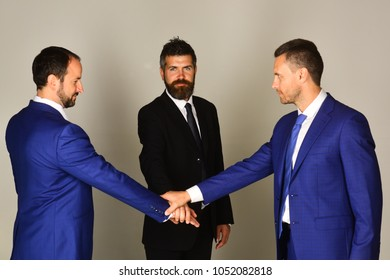 Businessmen wear smart suits and ties. Men with beard and serious faces make business deal and shake hands. Business and compromise concept. Executives settle agreements on light grey background