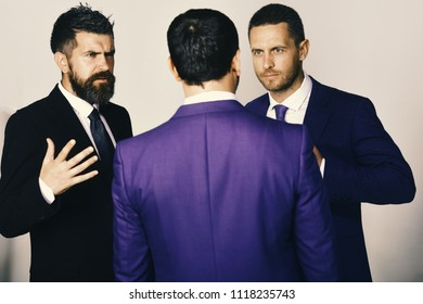 Businessmen wear smart suits and ties. Executives trying to find compromise on light grey background. Men with beard and convictive faces discuss leadership. Business Argument and business concept.
