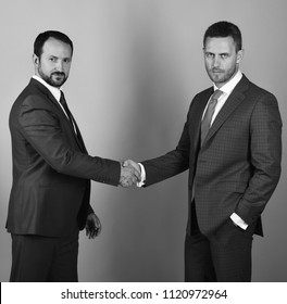 Businessmen wear smart suits and ties. Men with beard and serious faces make deal or agreement. CEOs shake hands on blue background. Business and compromise concept.