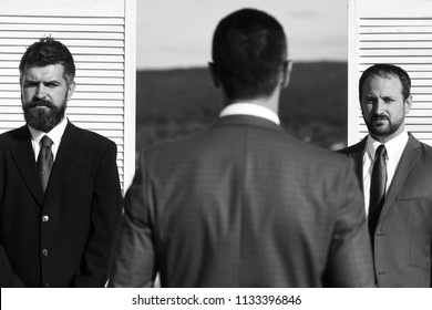 Businessmen wear smart suits and ties on wooden wall and nature background. Leaders with beard and serious faces discuss business. CEOs negotiate on partnership. Business and compromise concept.