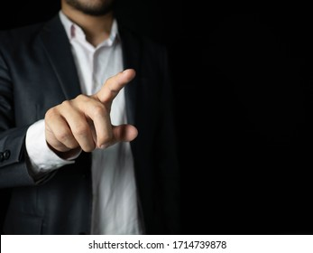 Businessmen wear suits pointing to touch something Is an object for graphic lines, able to add anything. With a black background, business, or financial concept.