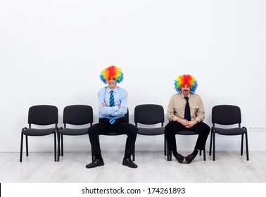 Businessmen wearing clown wigs waiting - sitting on row of chairs