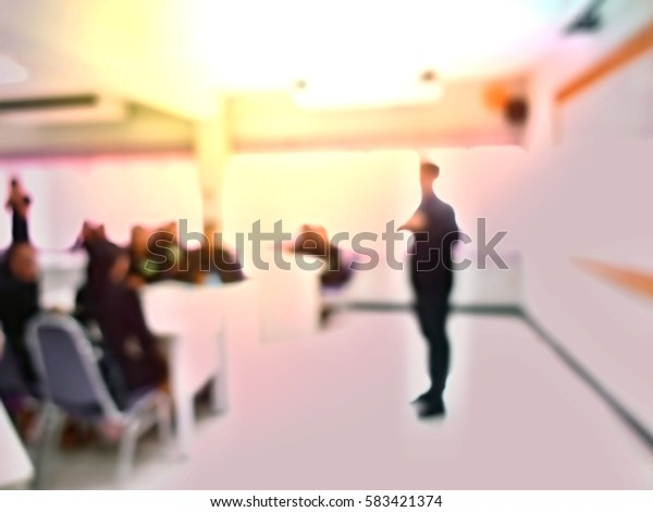 Businessmen and women blur in conference room presenting new product
