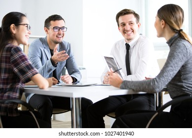 Businessmen working in an office sitting around a table