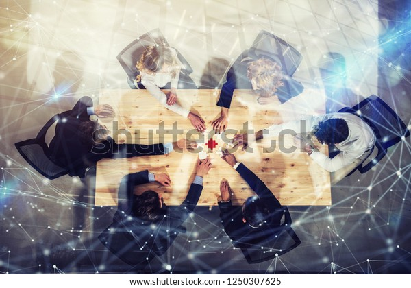 Businessmen working together to build a colored puzzle. Concept of teamwork, partnership, integration and startup. Double exposure with network effects