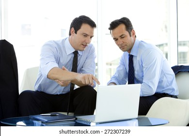 Businessmen working together on laptop in airport lounge