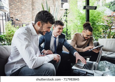 Businessmen are working together on wireless technology in a business meeting taking place in a bar courtyard.