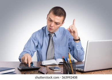 Business,office, technology, finances and internet concept - businessman at office holding finger up: idea or warning on gray background