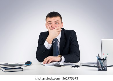 Business,office, technology, finances and internet concept - Serious businessman skeptically looking at you sitting at his desk on gray background.Human face expression