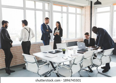 Businesspeople against the window. A team of young businessmen working and communicating together in an office. Corporate businessteam and manager in a meeting. Blured image.