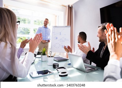Businesspeople Applauding Their Smiling Male Colleague After Presentation At Workplace