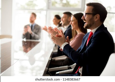 Businesspeople applauding while in a meeting at modern office