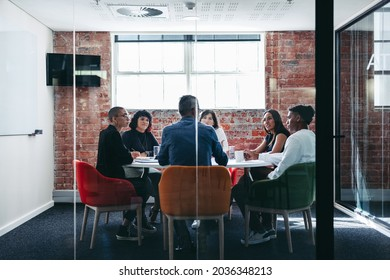 Businesspeople attending their morning briefing in a modern office. Group of creative businesspeople having a discussion during a meeting. Businesspeople working together as a team. - Shutterstock ID 2036348213