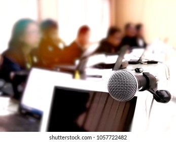 Businesspeople blurred in conference meeting room far from microphone in front