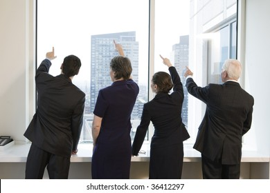 Businesspeople by window pointing up.