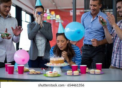 Businesspeople celebrating their colleagues birthday in office