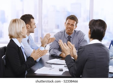 Businesspeople clapping hands, smiling and celebrating at meeting.