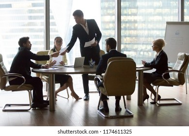 Businesspeople colleagues and black team leader discussing and reviewing report in meeting at conference room. Multiracial group professional share information and reach agreement and signing contract