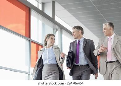 Businesspeople communicating while walking on railroad platform