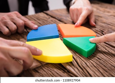 Businesspeople Connecting Pieces Of Multi Colored Pie Chart On Wooden Desk