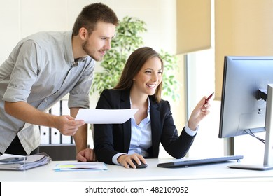 Businesspeople co-working comparing a desktop computer information with paper document at office