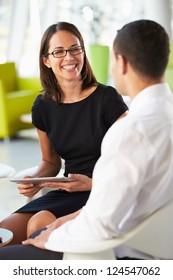 Businesspeople With Digital Tablet Having Meeting InOffice
