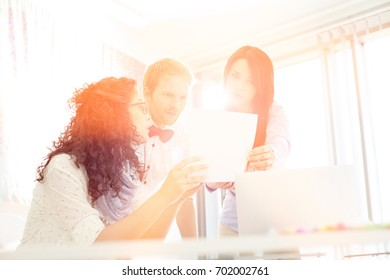 Businesspeople discussing over photograph in creative office