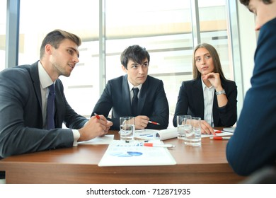 Businesspeople discussing together in conference room during meeting at office.