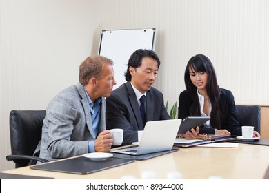 Businesspeople discussing while looking at electronic tablet