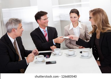 Businesspeople exchanging cards over coffee while having an informal meeting in a cafe
