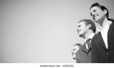businesspeople in formal wear standing together in line looking in same direction and smiling