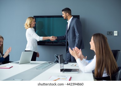 Businesspeople handshaking on a business meeting. Soft focus, high ISO, grainy image.