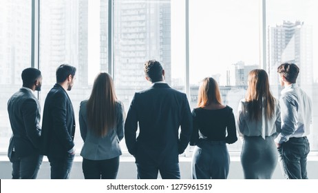 Businesspeople having break at meeting, looking through window, back view