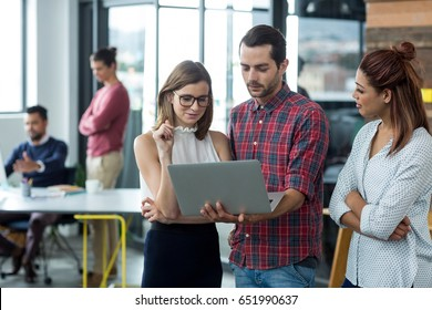 Businesspeople having discussion over laptop in office