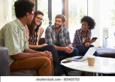Businesspeople Having Informal Meeting In Modern Office