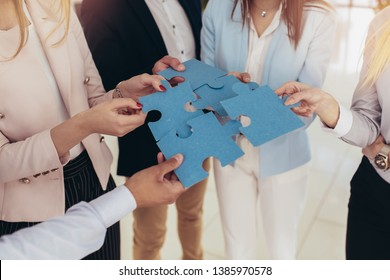 Businesspeople joining puzzle pieces in office