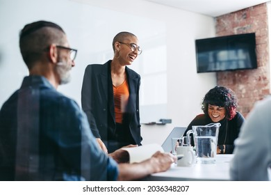 Businesspeople laughing during a briefing in an office. Group of successful businesspeople attending their morning meeting in a modern workplace. Creative businesspeople working together. - Shutterstock ID 2036348207