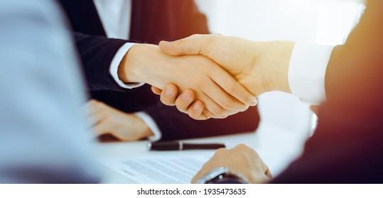 Geschäftsleute oder Rechtsanwälte, die sich in einem sonnigen Büro treffen oder verhandeln. Business-Handshake und Partnerschaft