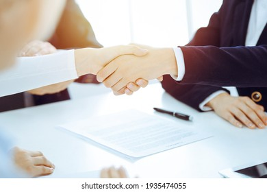 Businesspeople or lawyers shaking hands finishing up meeting or negotiation in sunny office. Business handshake and partnership