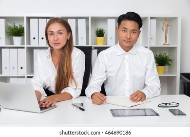 Businesspeople looking to camera sitting at office desk and working. She is typing. He is reading his notes. Concept of colaboration.