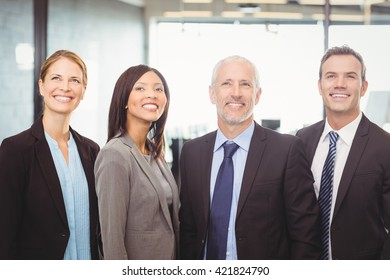 Businesspeople looking up and smiling in office