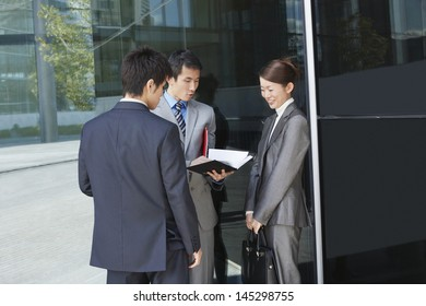 Businesspeople looking through documents outside office building