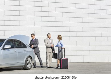 Businesspeople with luggage shaking hands outside car on street