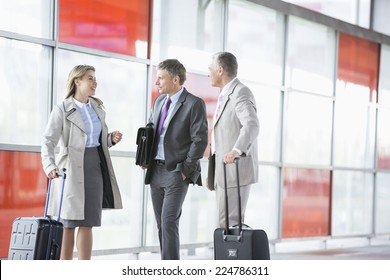 Businesspeople with luggage talking on railroad platform