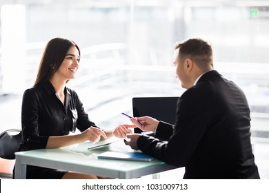 Businesspeople man and woman sitting at a table and signing a contract at office