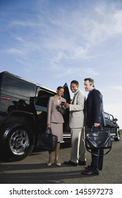 Businesspeople next to limousine