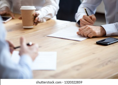 Businesspeople in office boardroom negotiating company representatives proving identities with signatures, signing affirm legal paper contract. Successful deal and obligations between parties concept