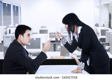 Businesspeople in an Office Fighting and Pointing Fingers at Each Other
